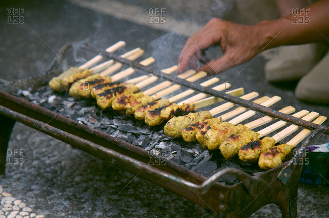 Cooking chicken satay on the grill