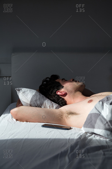 Young man sleeping next to his mobile phone