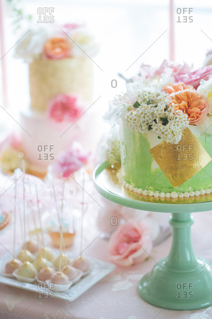 Cake pops beside a green and gold cake topped with flowers