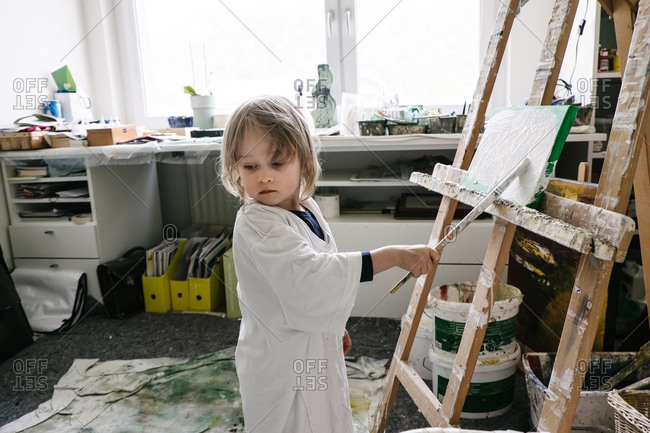 Toddler painting a picture on an easel