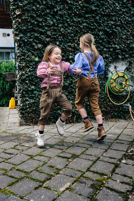 Sisters skipping arm in arm while wearing lederhosen