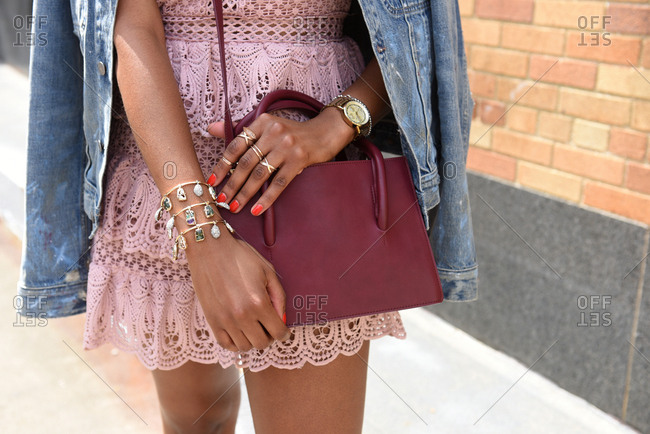 Fashionable woman wearing a pink lace dress with a maroon purse and gold jewelry