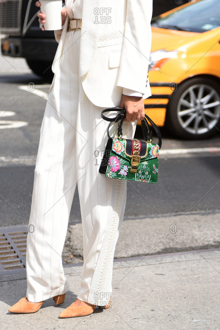 New York, NY, USA - September 12, 2017: Fashionable woman wearing white suit and holding a colorful handbag
