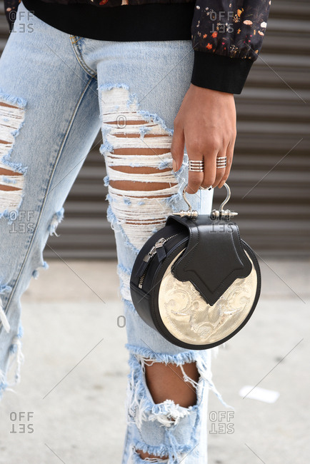 New York, NY, USA - September 12, 2017: Woman wearing ripped jeans holding a black and metallic handbag