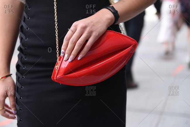New York, NY, USA - September 12, 2017: Woman at New York Fashion Week in black laced up skirt wearing a red lips purse