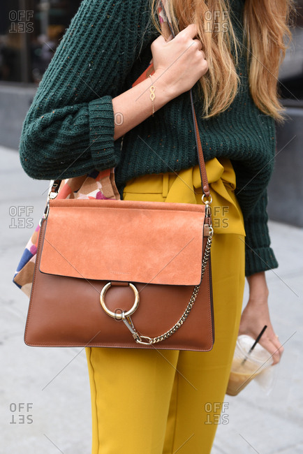 New York, NY, USA - September 12, 2017: Trendy street style woman with yellow pants and a brown leather bag
