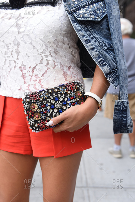 New York, NY, USA - September 12, 2017: Woman in red shorts and denim jacket holding a colorful sequins clutch