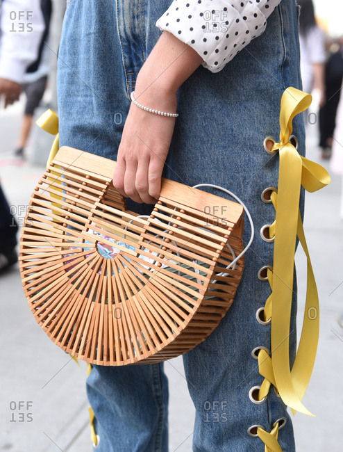 New York, NY, USA - September 12, 2017: Woman in denim overalls holding a bamboo wood clutch