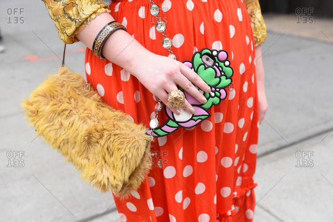 New York, NY, USA - September 12, 2017: Woman wearing a red polka dot skirt with a faux fur handbag
