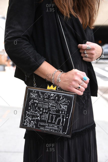 New York, NY, USA - September 12, 2017: Woman all in black with a black graphic purse and silver jewelry