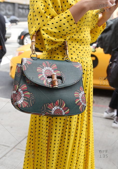 New York, NY, USA - September 12, 2017: Woman wearing a yellow polka dot dress with a green handbag