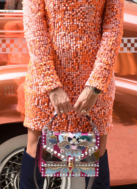 New York, NY, USA - September 12, 2017: Woman in orange sequins dress standing next to an antique car with a colorful handbag