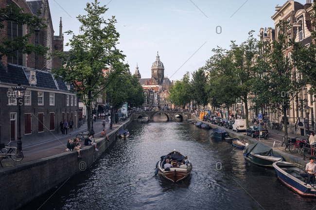 Amsterdam, Netherlands - July 29, 2014: Boat on Amsterdam canal heading towards Sint-Nicolaaskerk