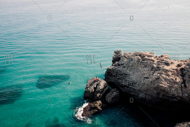 People diving from cliffs into azure blue ocean water