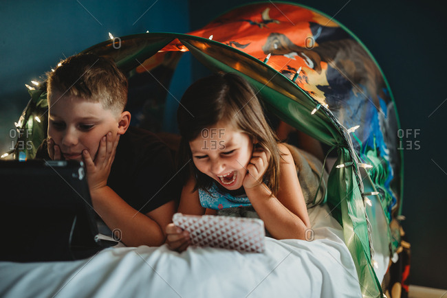 Siblings watching media in a tent bed