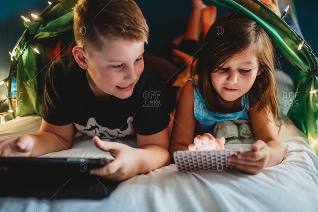 Siblings play with devices in a tent bed