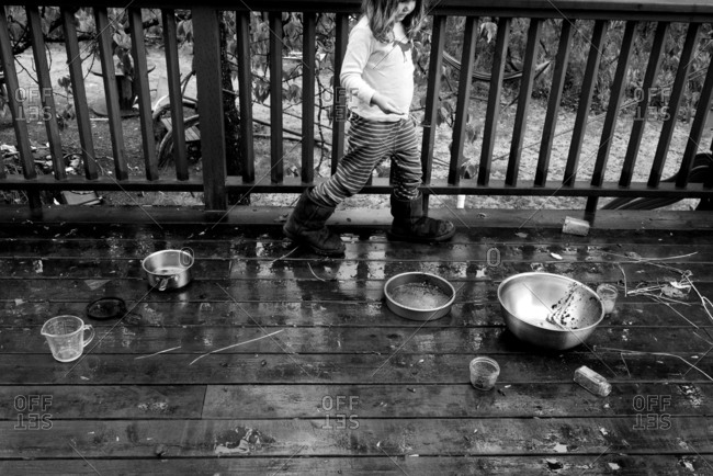 Girl by bowls on wet porch
