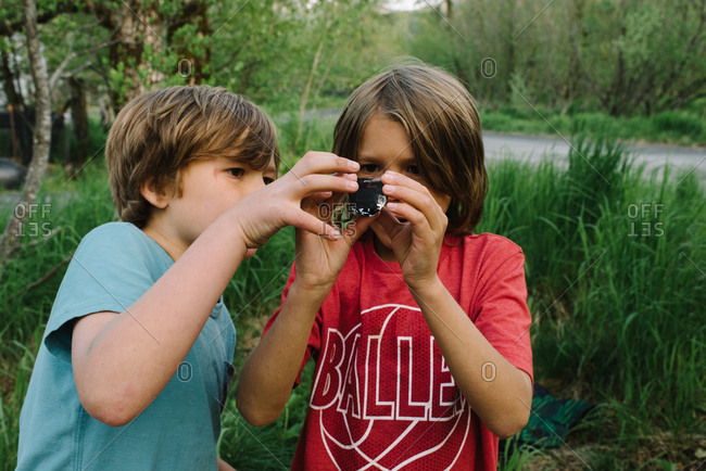 Two boys taking apart a camera