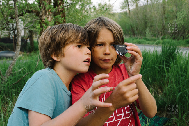 Two boys looking at piece of plastic