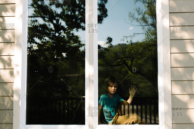Boy in a window of home