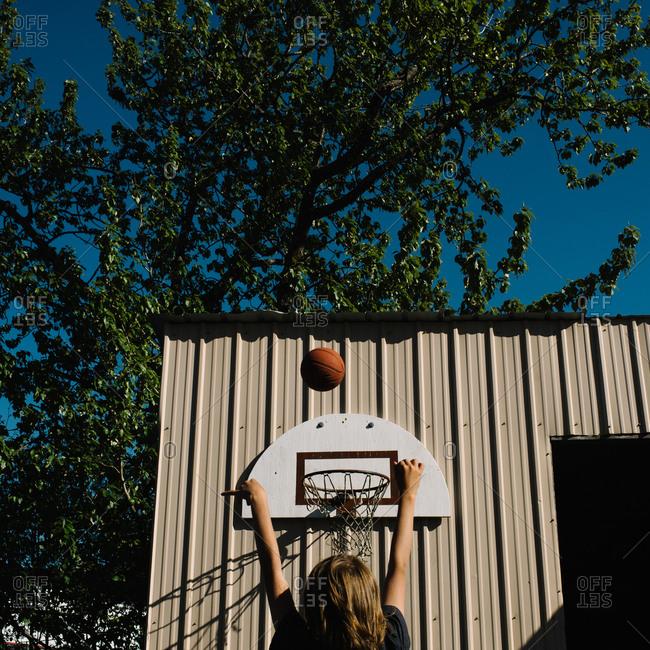 Boy throwing basketball to a hoop