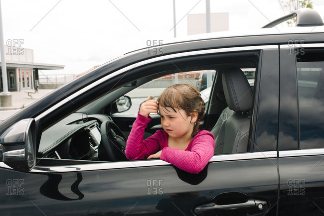 Girl staring out from front seat of car