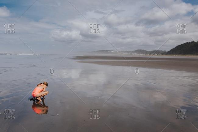 Girl kneeling on beach in Washington