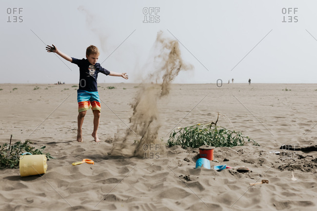 Boy throwing sand on a beach