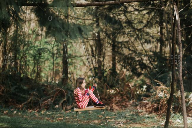 Girl on swing eating popsicle