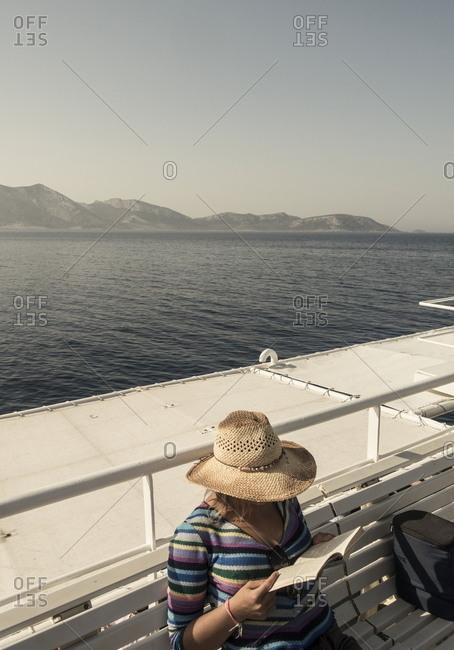 Cyclades, Greece - July 26, 2017: Woman on ferry boat in Aegean sea