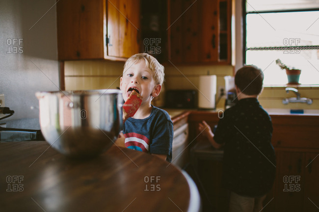 Boys licking batter in kitchen