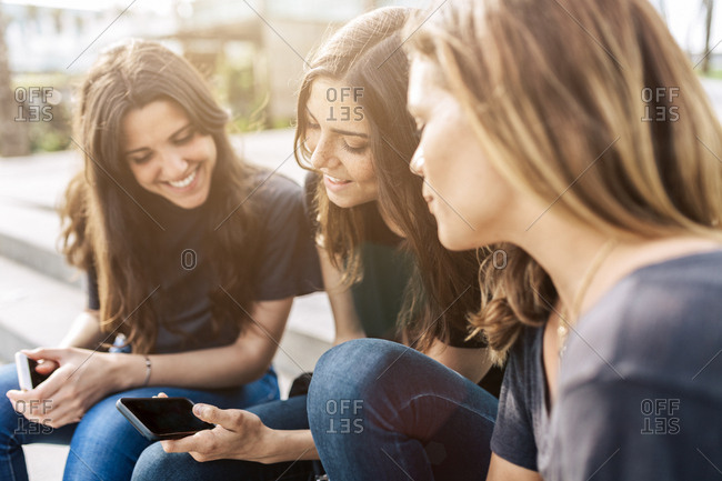 Three happy young women sitting outdoors looking at cell phone