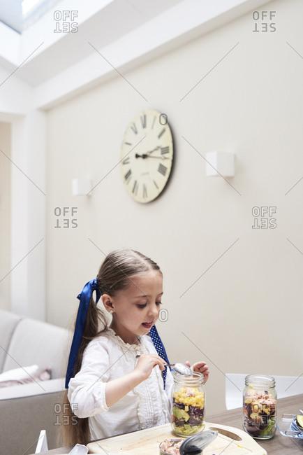 Little girl preparing healthy salad in the kitchen