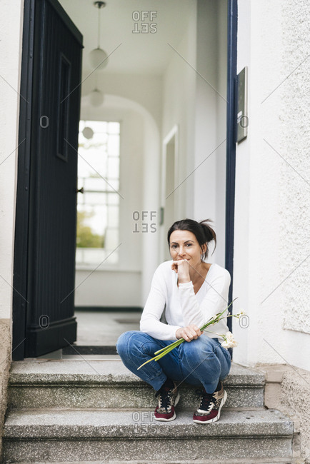 Woman with flowers sitting on doorstep