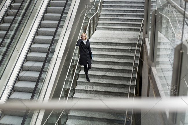 Businesswoman on stairs with cell phone