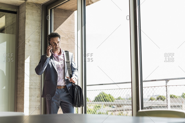 businessman standing by window- making a phone call