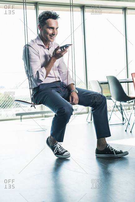 Businessman in office sitting on swing- using smartphone