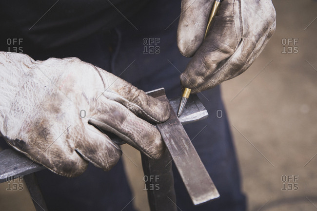 A blacksmith is taking measures on a piece of metal in a workshop