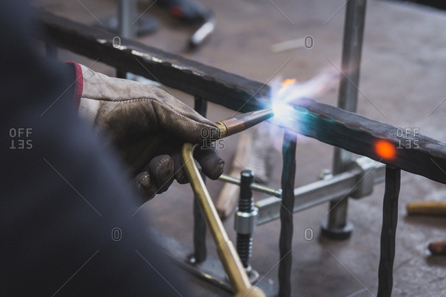 A blacksmith in a leather apron is using a cutting torch in his workshop