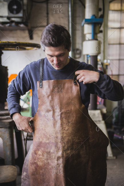 A blacksmith puts on a leather apron in a workshop
