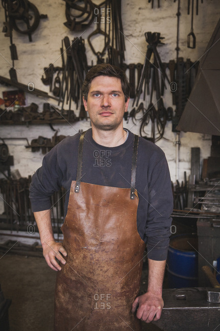 A blacksmith wears a leather apron and is portrayed in his workshop