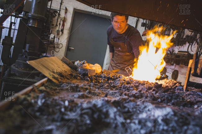 A blacksmith is heating up an iron bar in a workshop