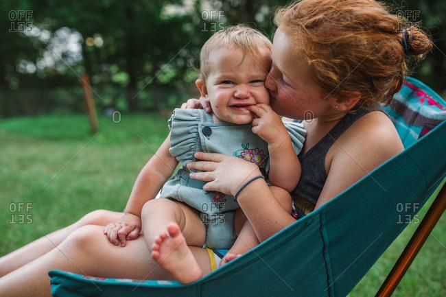 Girl kissing baby sister on backyard chair