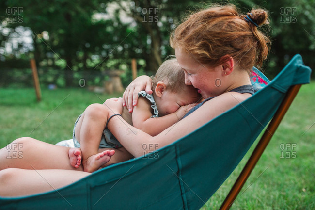 Girl cuddling with baby sister on backyard chair