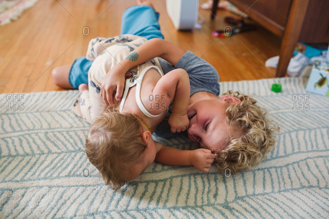 Boy rolling around on floor with baby sister