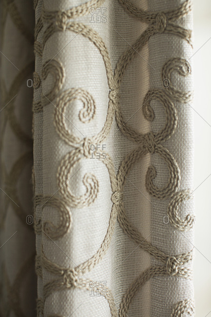 Close up of curtains with embroidered swirl pattern