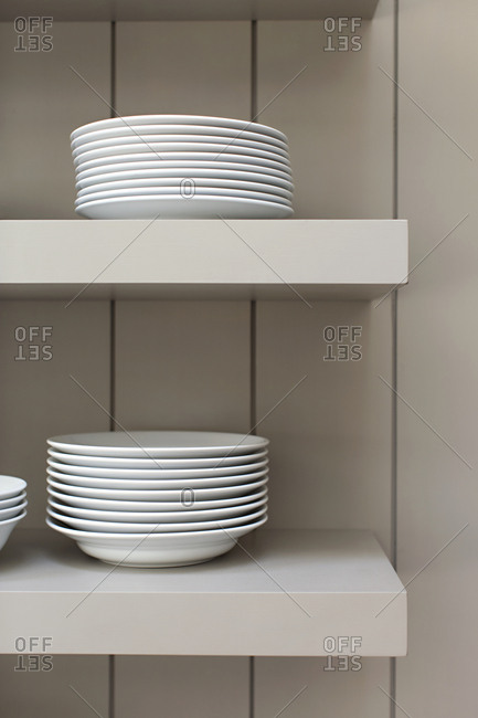 Plates and bowls stacked on white shelves