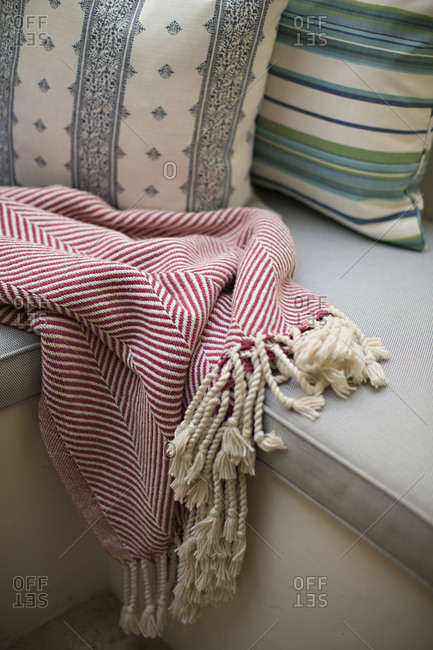 Bred blanket with tassels on seat with cushion and pillows
