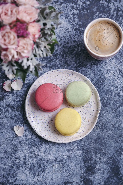 Macaroons on a dessert plate and a cup of coffee on grey background