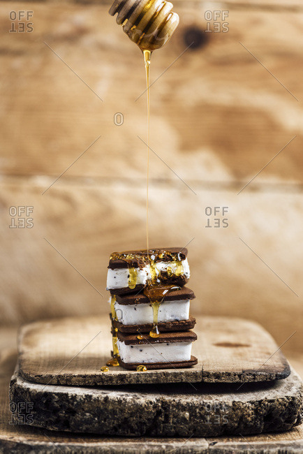 Ice Cream Sandwiches are piled on one another and drizzled with honey on a wooden board